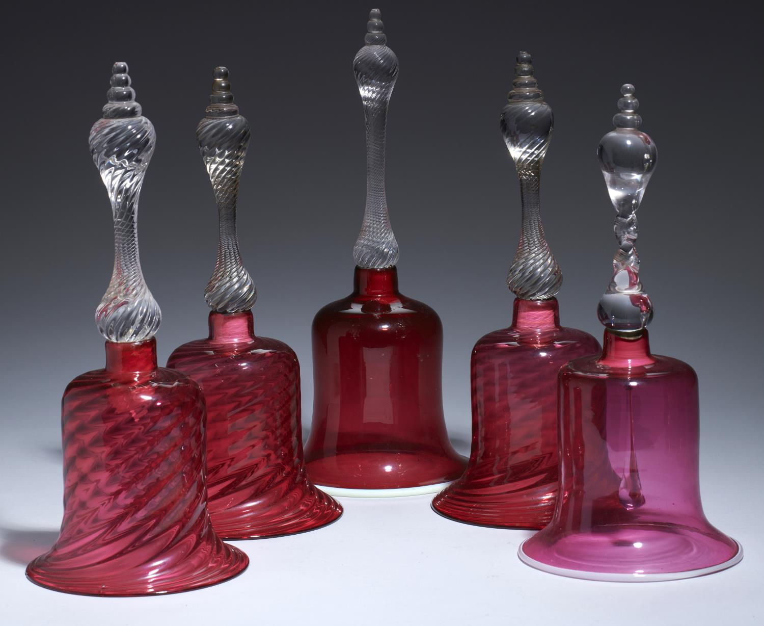 Lot 387 - FIVE VICTORIAN CRANBERRY GLASS BELLS, MID 19TH C with clear spiral handle, 30-34cm h, all but one