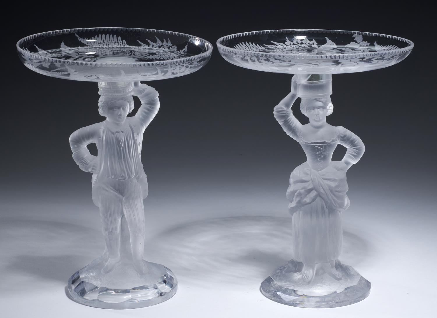 Lot 380 - A PAIR OF JOHN FORD OF EDINBURGH MAN AND WOMAN FIGURAL MOULDED GLASS STANDS OR CANDLESTICKS AND PAIR