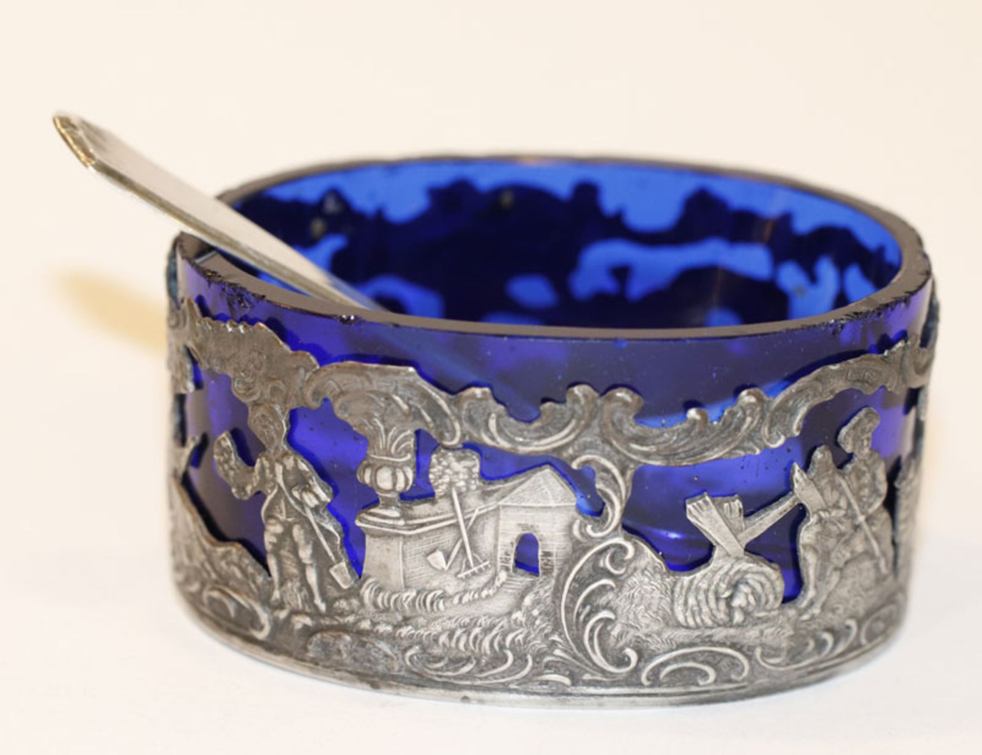 Salzgefäß, 800 Silber mit figürlichen Szenerien und Salzlöffel, blauer Glaseinsatz, bestossen