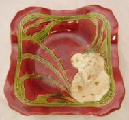 A Minton secessionist square dish decorated with a wild rose on a red ground CONDITION