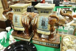 A pair of glazed pottery elephant vase stands or stools