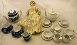A circa 1900 biscuit fired porcelain headed doll in long white dress with cloth body together with