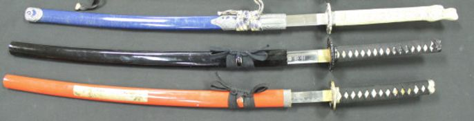 Three modern Japanese katanas with lacquered scabberds one with simulated ivory handle on a display