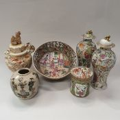 A pair of 19th Century Chinese famille rose baluster shaped vases and covers with all over panel