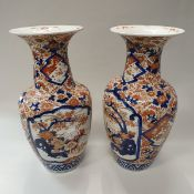 A pair of Japanese Meiji period Imari vases with all over foliate decoration and panels of