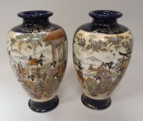 A pair of early 20th Century Japanese Satsuma vases decorated with panels of figures,
