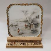 A Japanese porcelain polychrome decorated rectangular tray depicting a family group by waters edge
