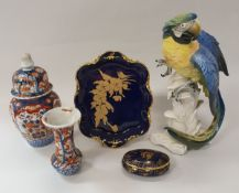 A Karl Ens macaw figure, two Meissen onion pattern leaf dishes,