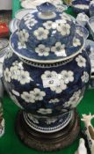 A 19th Century Chinese blue and white prunus blossom decorated baluster shaped vase and cover on a