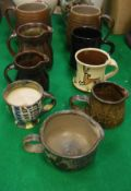 A collection of various studio pottery including two Poole Sylvan ware M70 mugs,