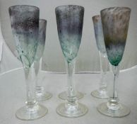 A set of six Tysoe glass flutes of iridescent bubble form raised on a circular foot,