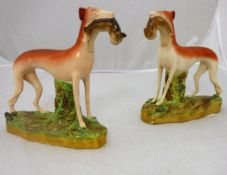 """A pair of Victorian Staffordshire figures of """"Greyhounds with hare quarry"""""""