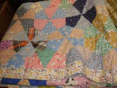 A mid-20th Century patchwork quilt in pink, yellow, green,