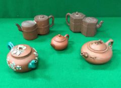 A collection of five Chinese Yi Xing teapots including a double chambered example with reeded