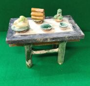 A Chinese Ming Dynasty model of an altar table with green and brown glazed models of offerings