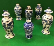 A pair of 19th Century Chinese blue and white baluster shaped vases and covers decorated with four