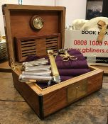 A walnut humidor together with two silver single cigar holders, ten plated single cigar holders,