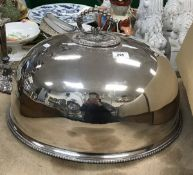 A large oval plated food dome with beade