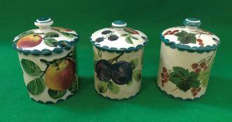 Three Wemyss preserve pots with lids, on