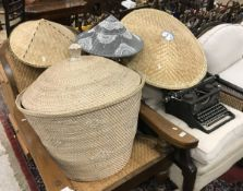A cane work lidded basket together with three caned hats of small proportion and a larger hat,