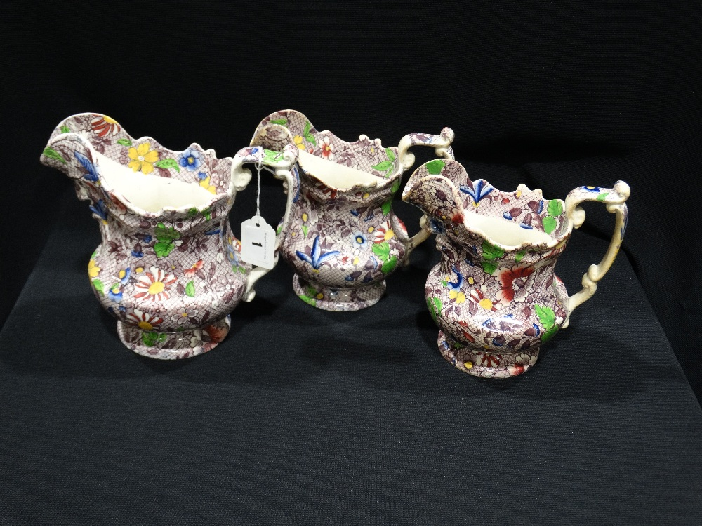 Lot 1 - Three Matching Staffordshire Pottery Mask Head Jugs With Floral Transfer Decoration