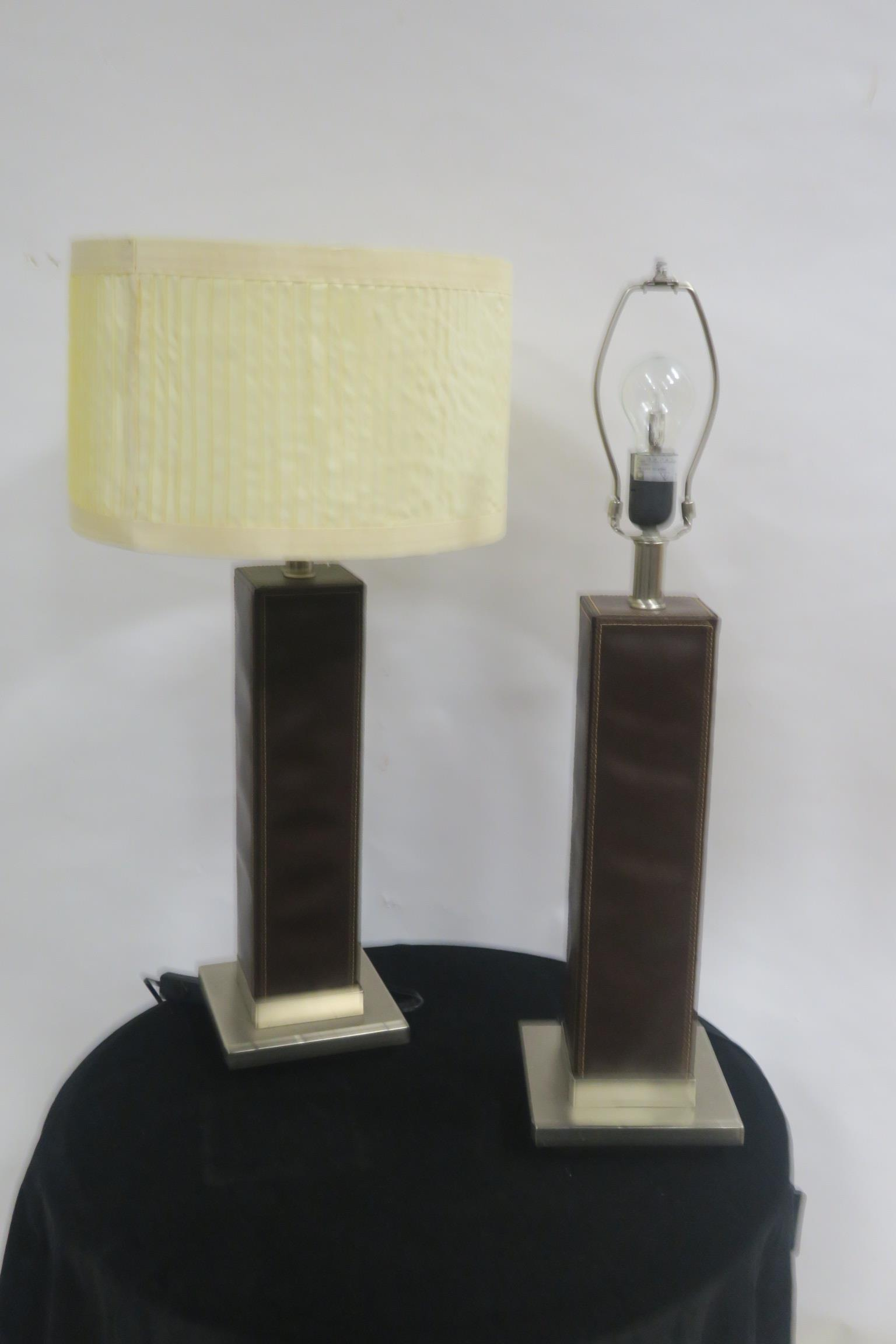 Lot 124 - A PAIR OF CHROME AND HIDE UPHOLSTERED TABLE LAMPS each of rectangular form with pleated shade 74cm