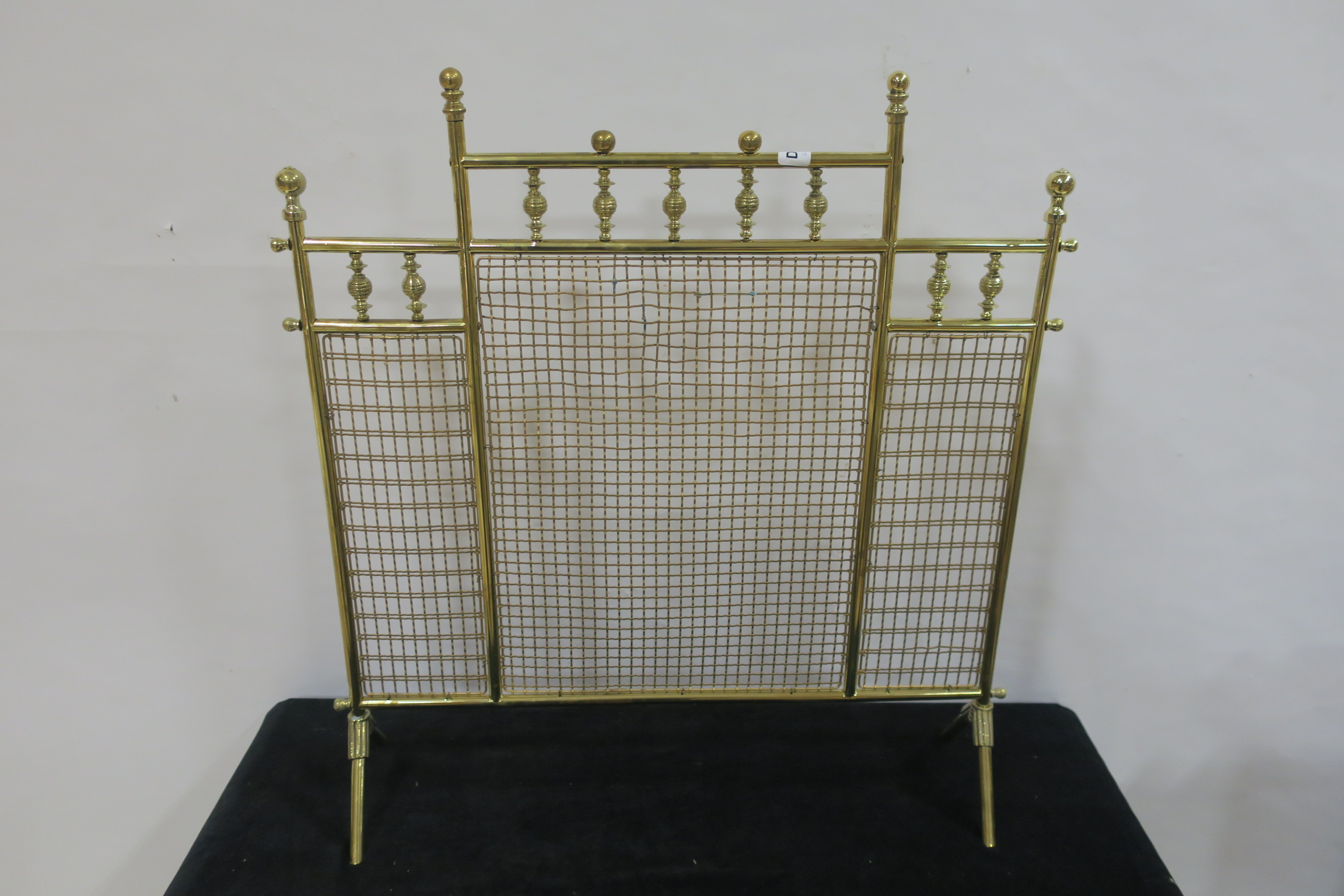 Lot 405 - A BRASS MESH FIRE SCREEN with knob finials raised on splayed legs 68cm x 65cm