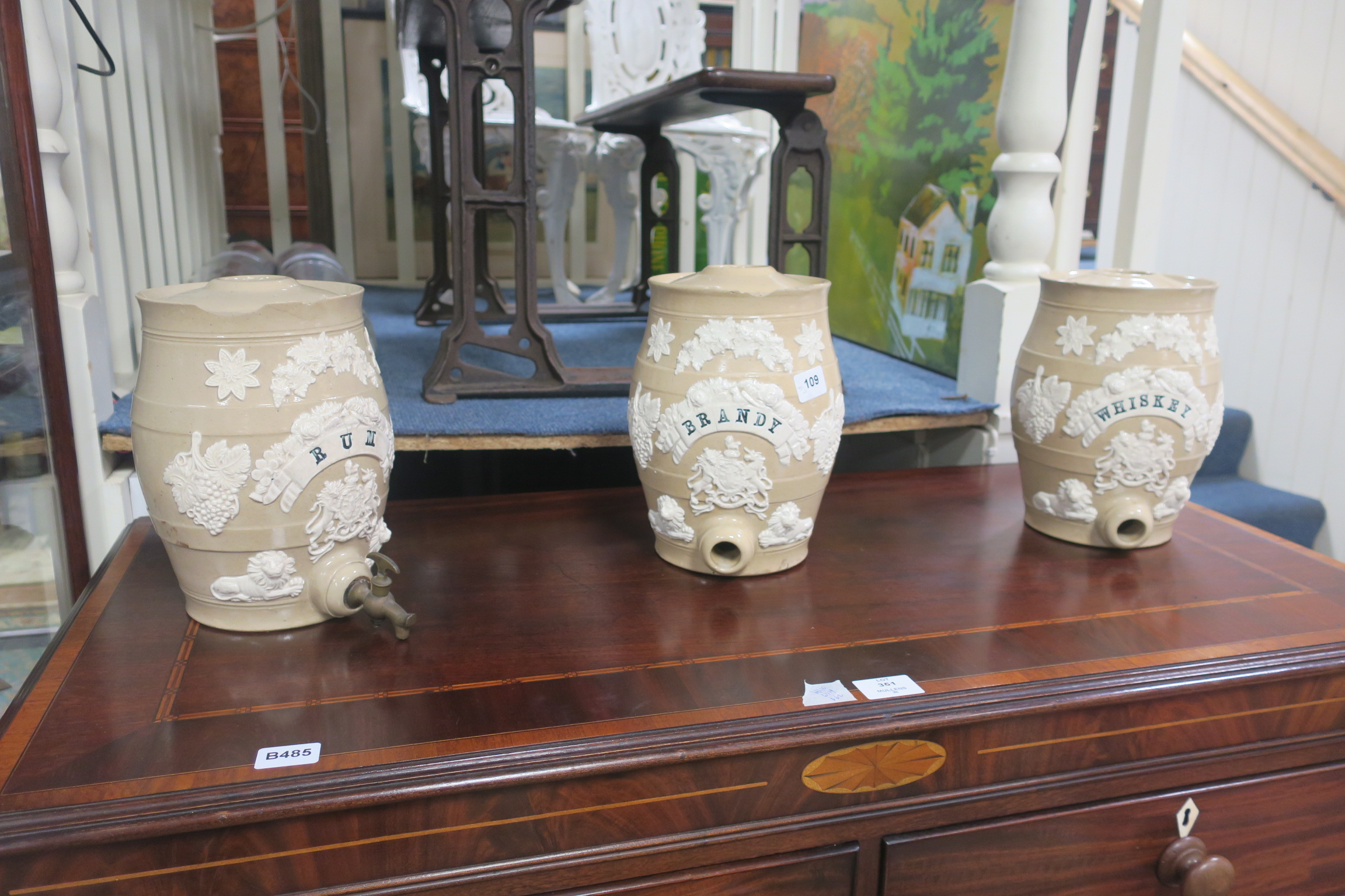 Lot 714 - A SET OF THREE 19th CENTURY SPIRIT BARRELS, each of ovoid form moulded in relief with foliage,