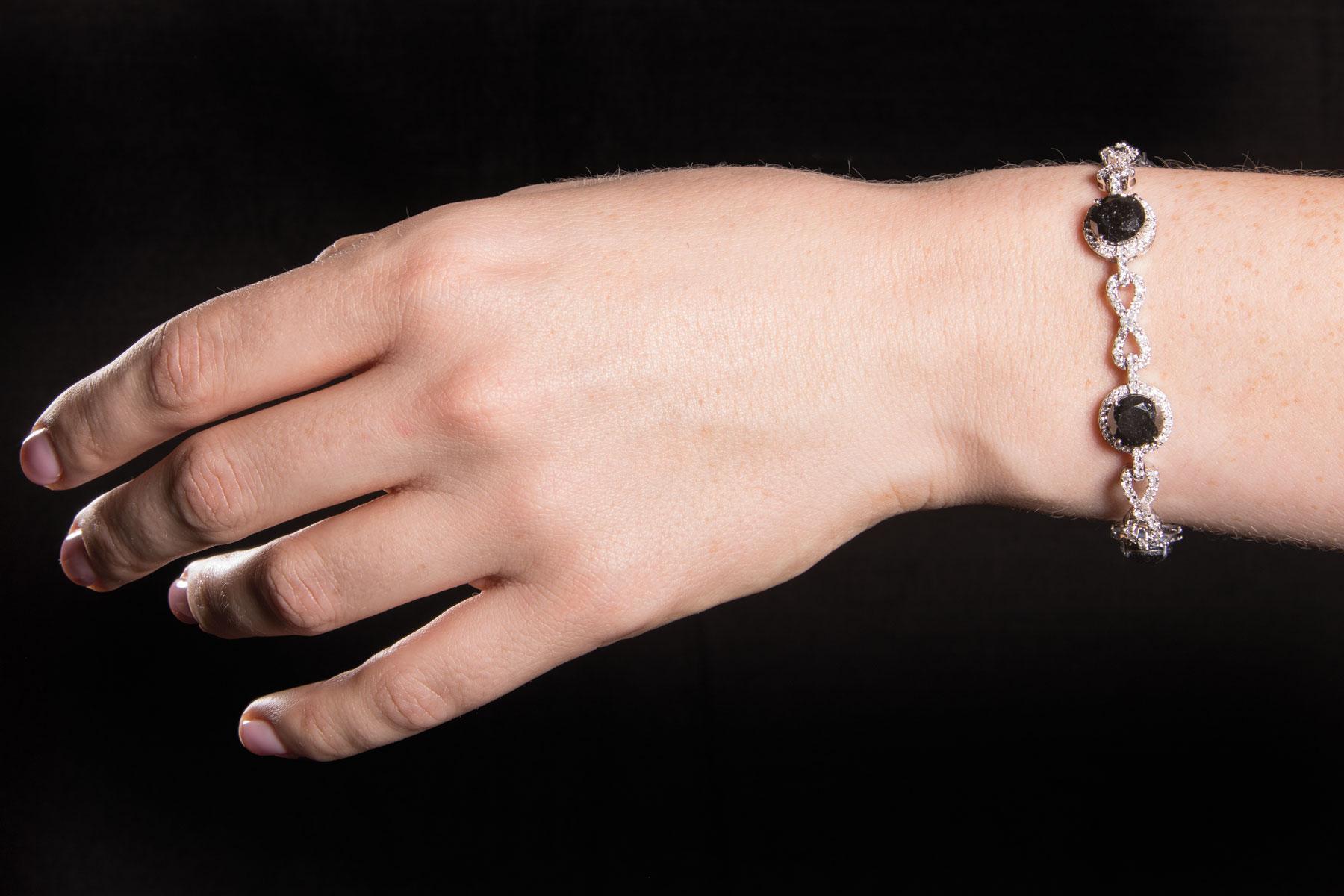 Lot 619 - 14 kt. White Gold, Black Diamond and Diamond Bracelet , 6 round brilliant cut black diamonds, 7.8-