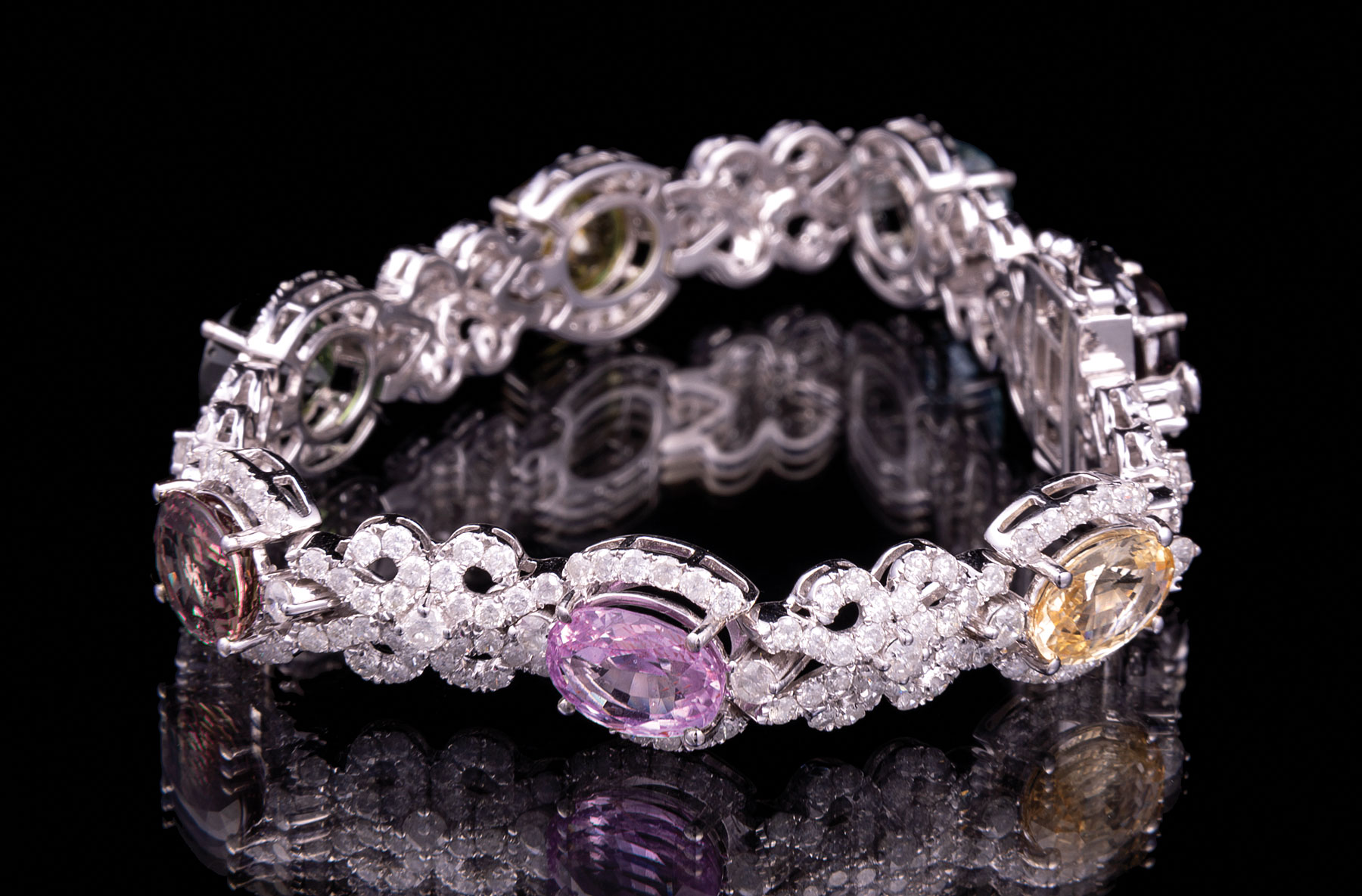 Lot 615 - Rare 14 kt. White Gold, Sapphire and Diamond Bracelet , seven prong set oval mixed cut multicolor