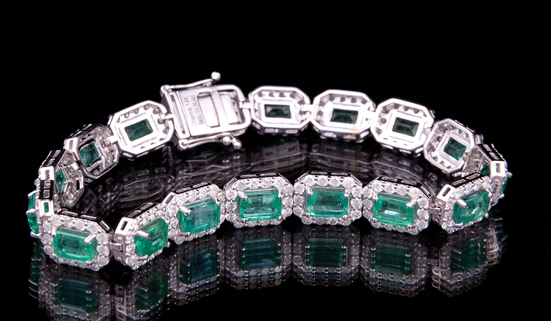 Lot 582 - 14 kt. White Gold, Emerald and Diamond Bracelet , 17 prong set rectangular step cut natural