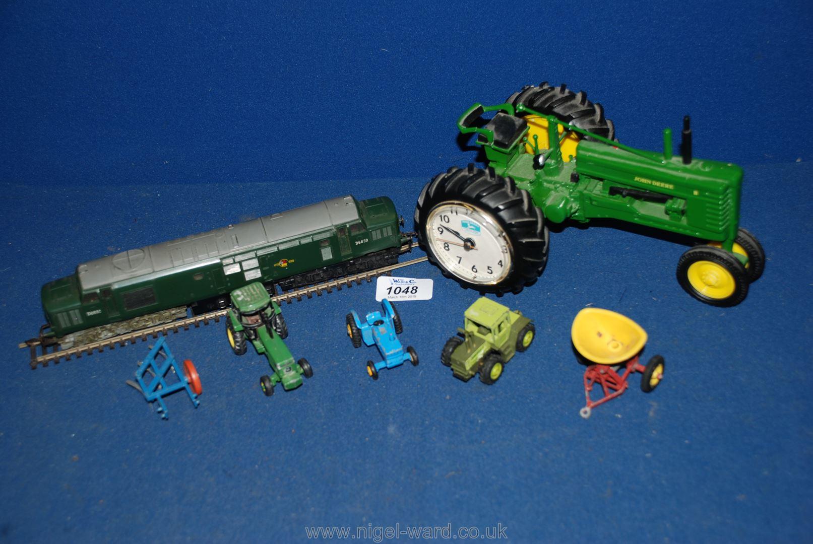 Lot 1048 - A John Deere tractor/clock and various miniature tractors.