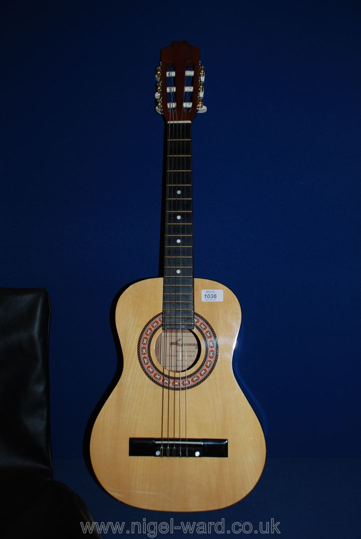Lot 1036 - A child's acoustic Guitar in a soft carrying case; needs a new E (first) string.