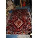 Lot 1023 - A red patterned wool Rug.