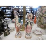 A pair of glazed pottery figures in 18th Century costume both damaged