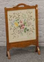 Lot 257 - An oak cased firescreen with embroidered panel.