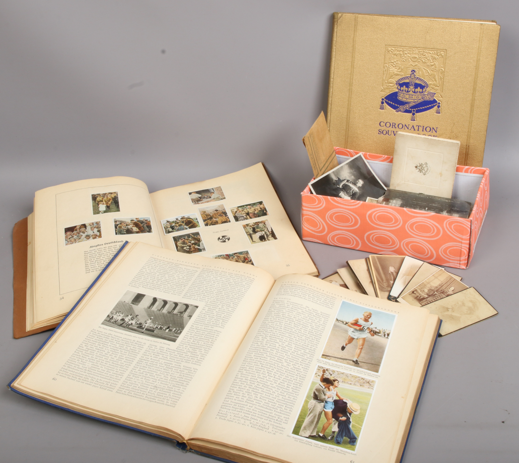 Lot 35 - A box of vintage photographs, along with three vintage books Coronation Souvenir 1937, Olympia