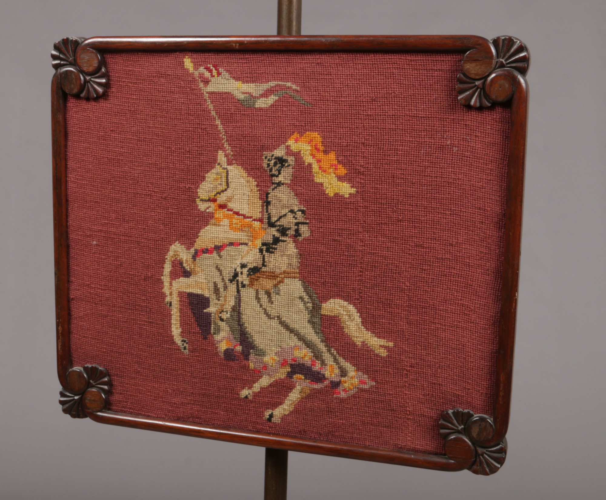 Lot 699 - A Regency mahogany pole screen set with a woolwork panel of a knight on horseback.