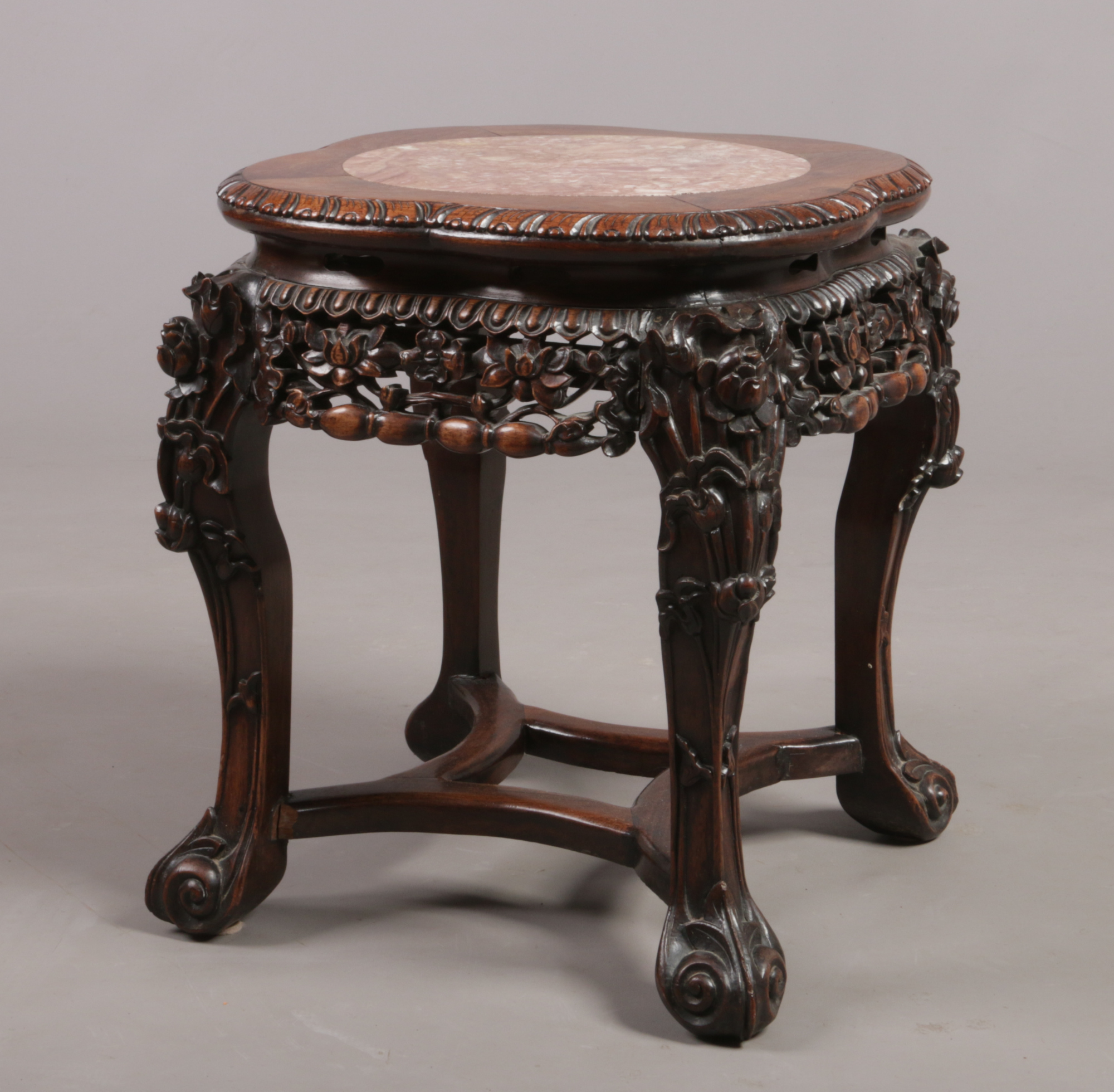Lot 541 - A 19th century Chinese hardwood and pink marble vase stand. With gadrooned quatrefoil top, foliate