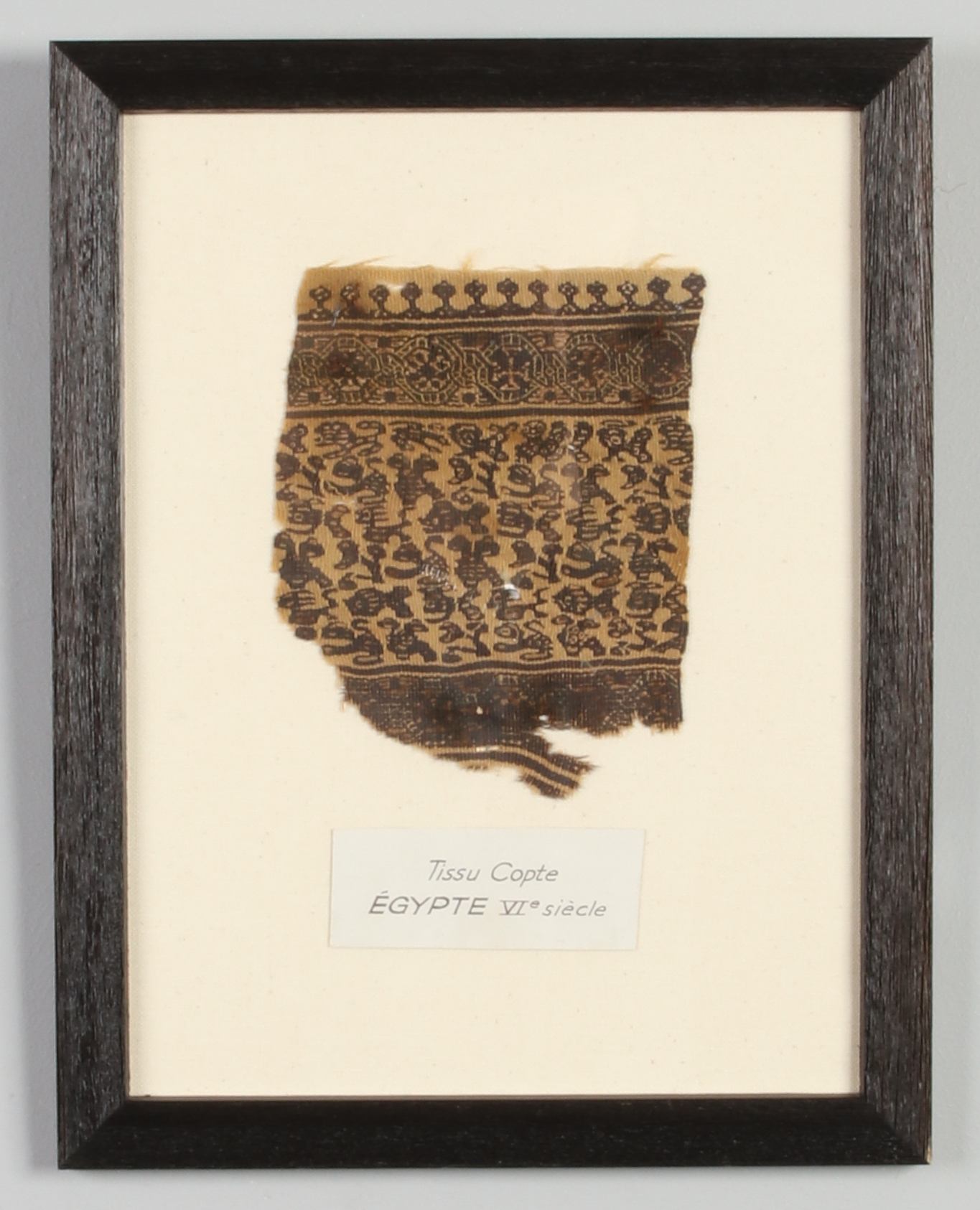 Lot 476 - A framed fragment of Coptic textile, Egypt 6th century. Label reads Tissu Copte, Egypte VIe