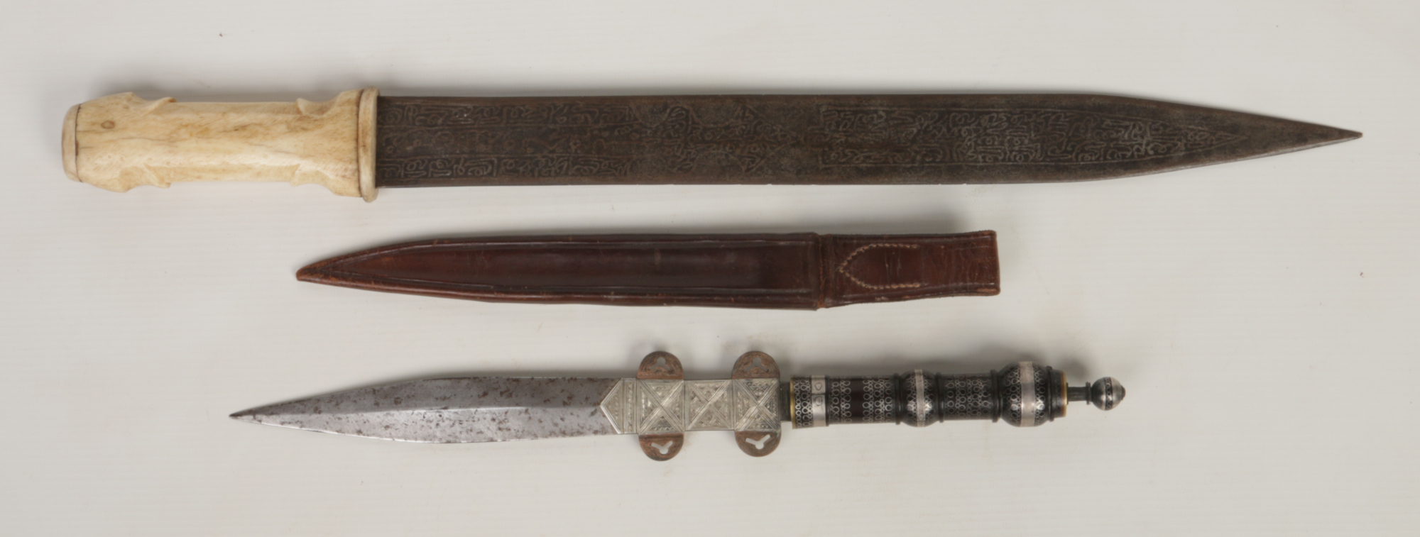 Lot 263 - A 19th century Eastern hunting knife in associated leather sheath, with turned hardwood grip