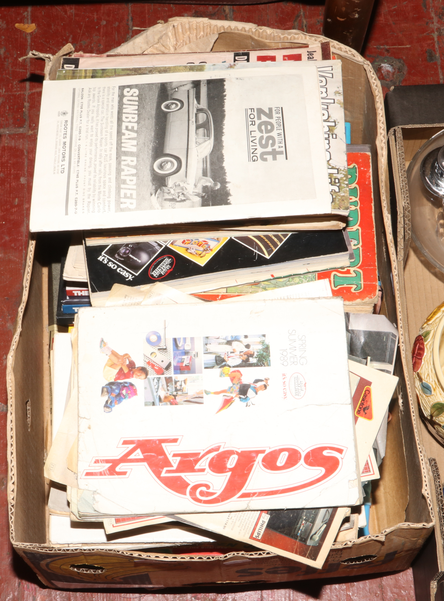Lot 560 - A box of c1980s catalogues, magazines, childrens annuals and games.