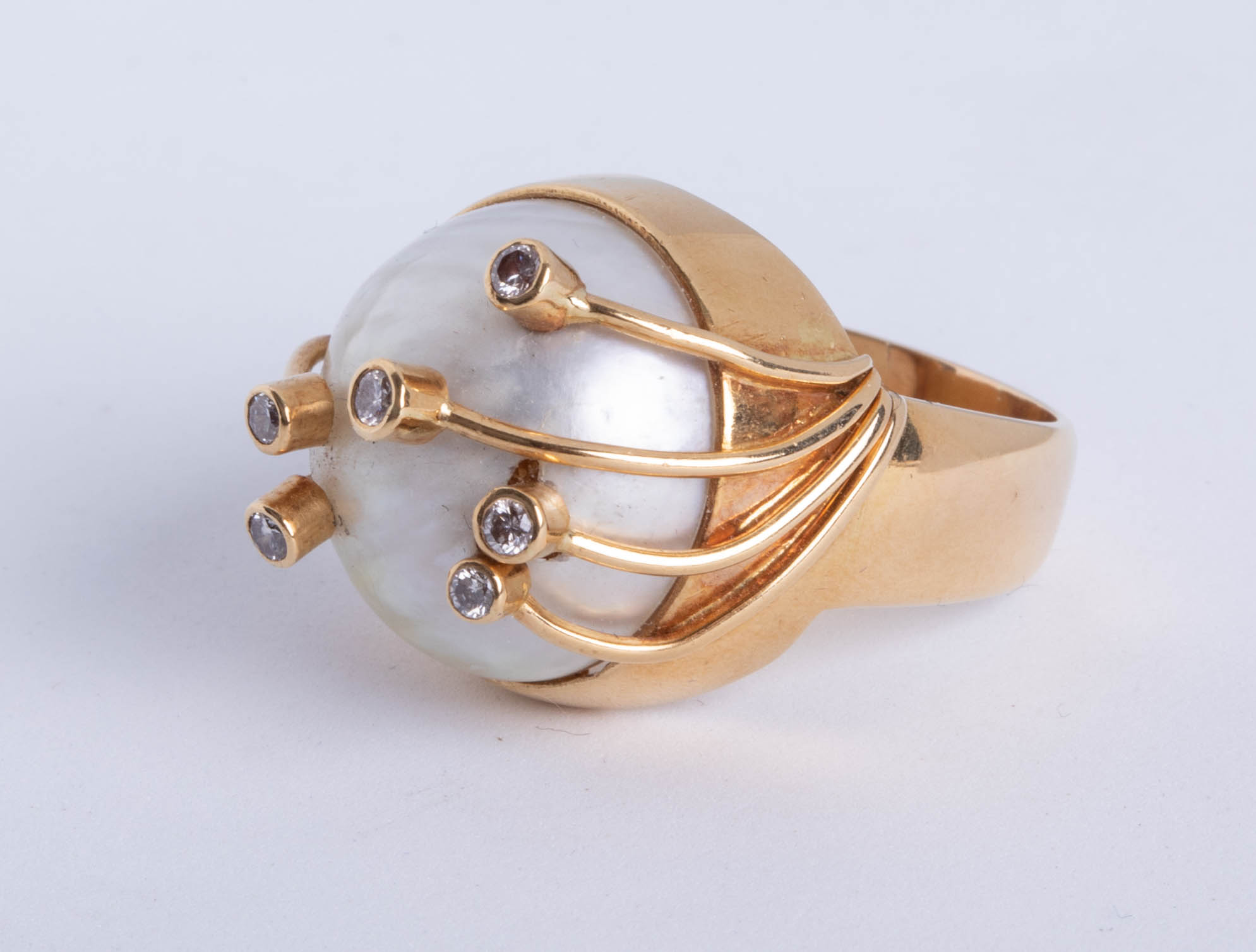 Lot 026 - An impressive Mabe pearl ring set with diamonds in yellow gold, size U.