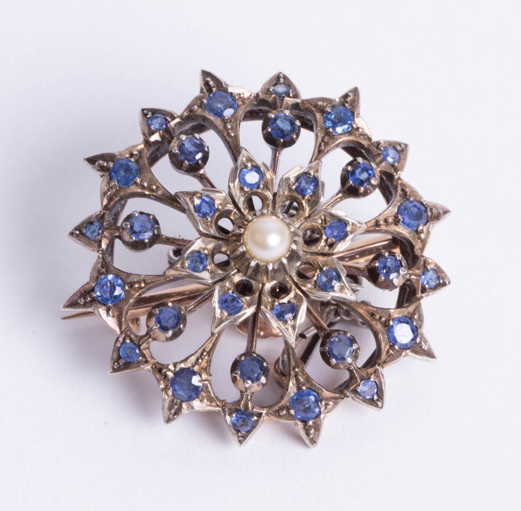 Lot 035 - An unmarked yellow metal sapphire and pearl set open circular flower brooch, diameter 34mm.