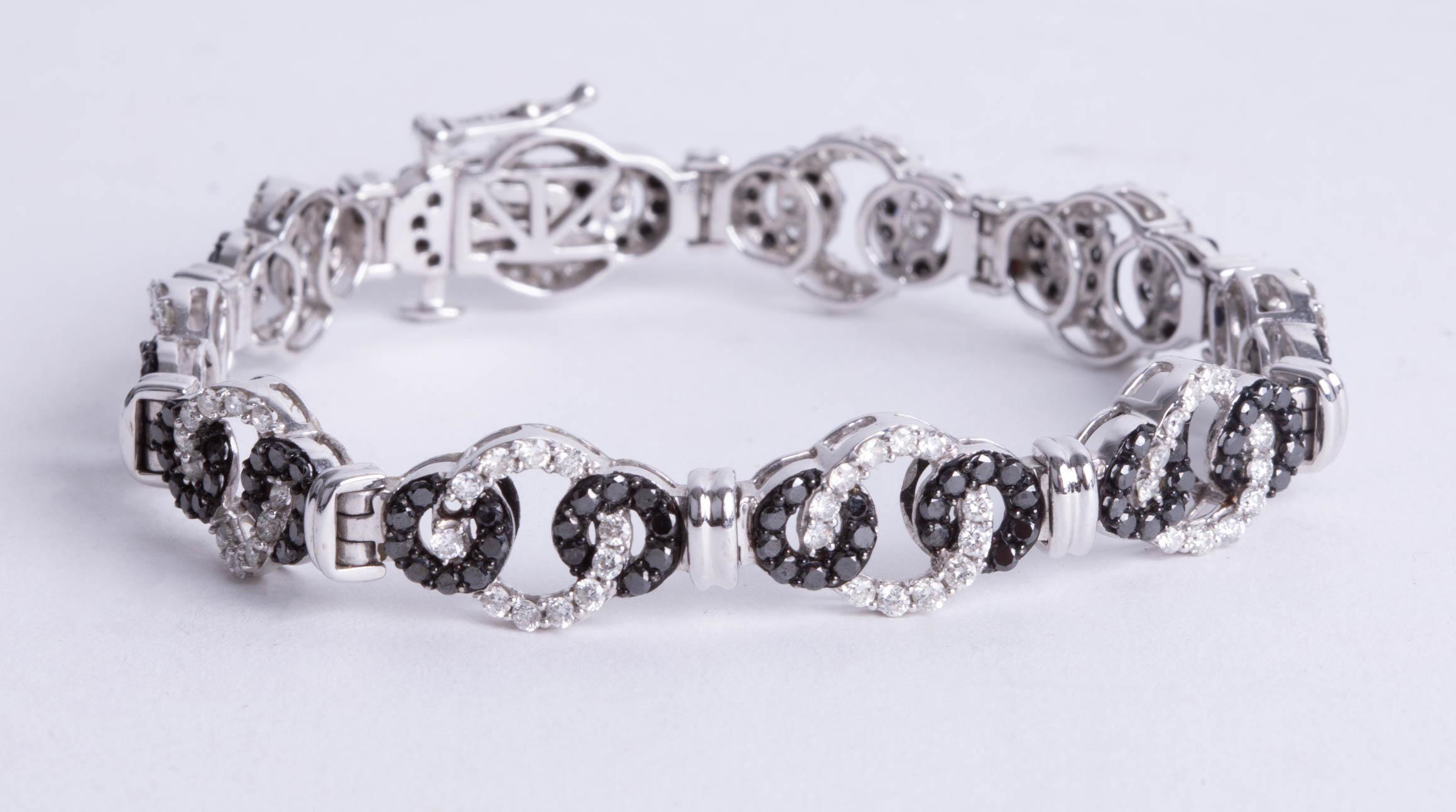 Lot 024 - A contemporary white gold black and white diamond bracelet, length 19cm.