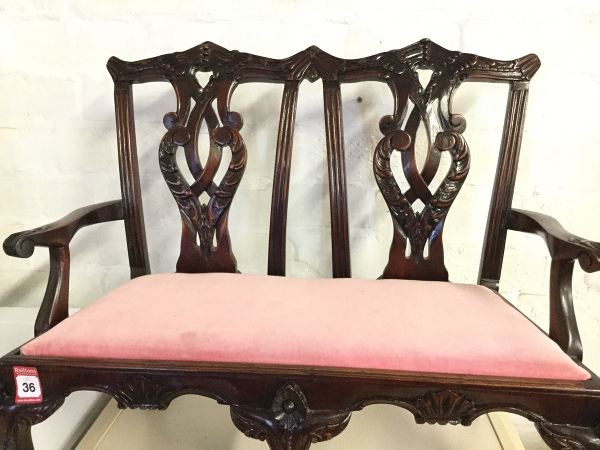 Lot 36 - A Chippendale style carved mahogany miniature settee, the twin back with pierced leaf scrolled