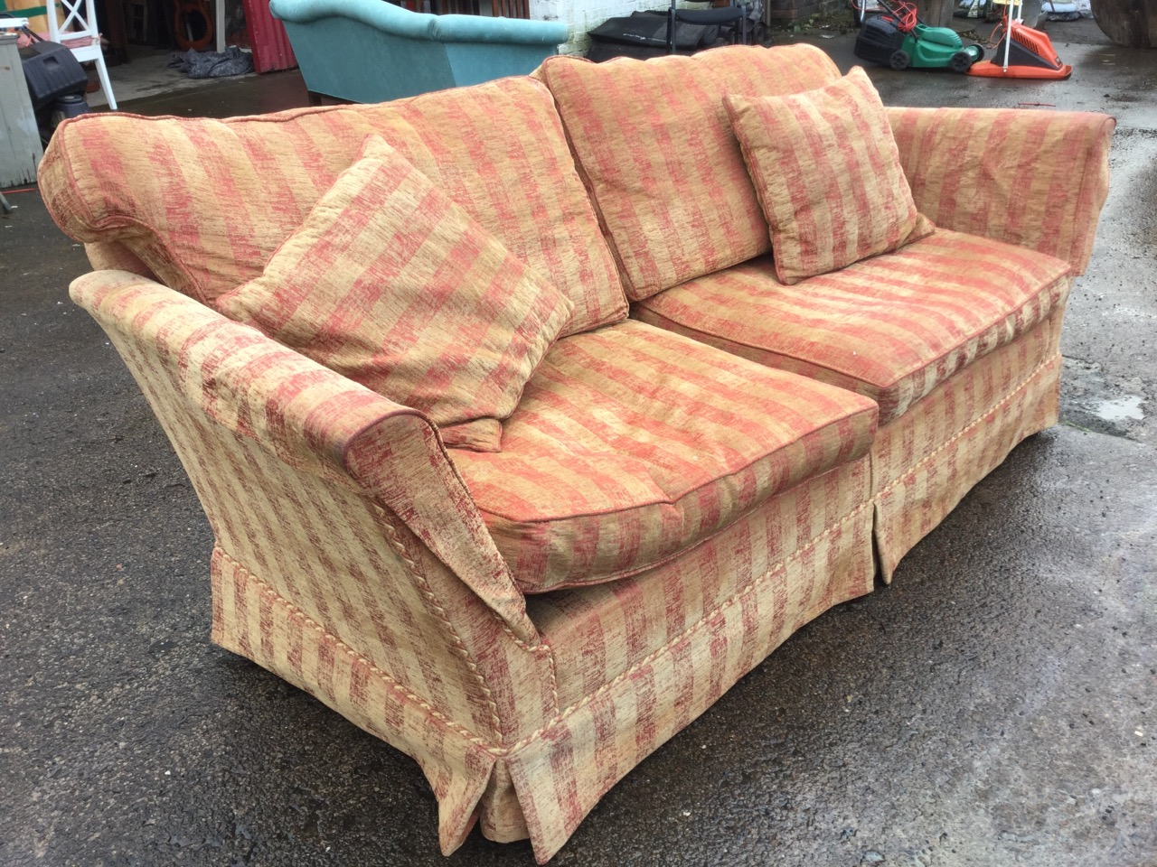 Lot 24 - A contemporary sofa upholstered in striped gold & maroon brushed velour, having loose cushions and