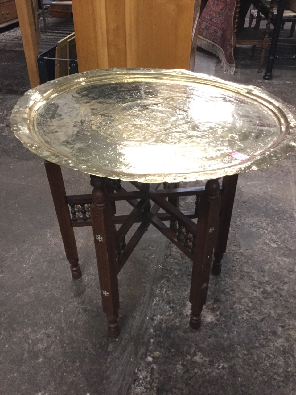 Lot 8 - A circular eastern tray-top brass coffee table, engraved with couple in arched panel flanked by