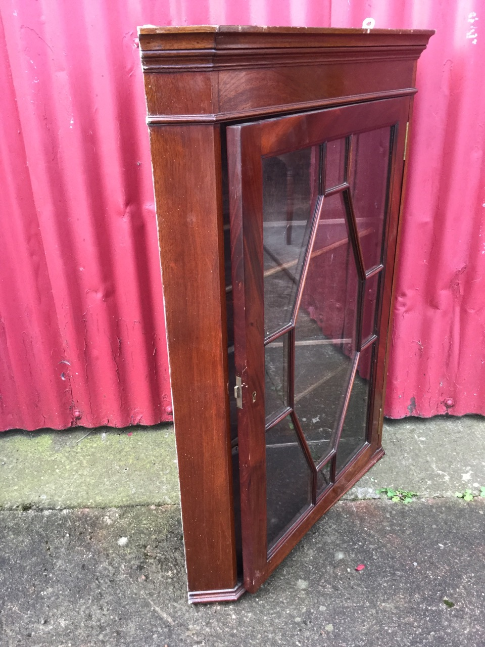 Lot 44 - A Victorian mahogany corner cabinet with moulded cornice above astragal glazed door framed by canted