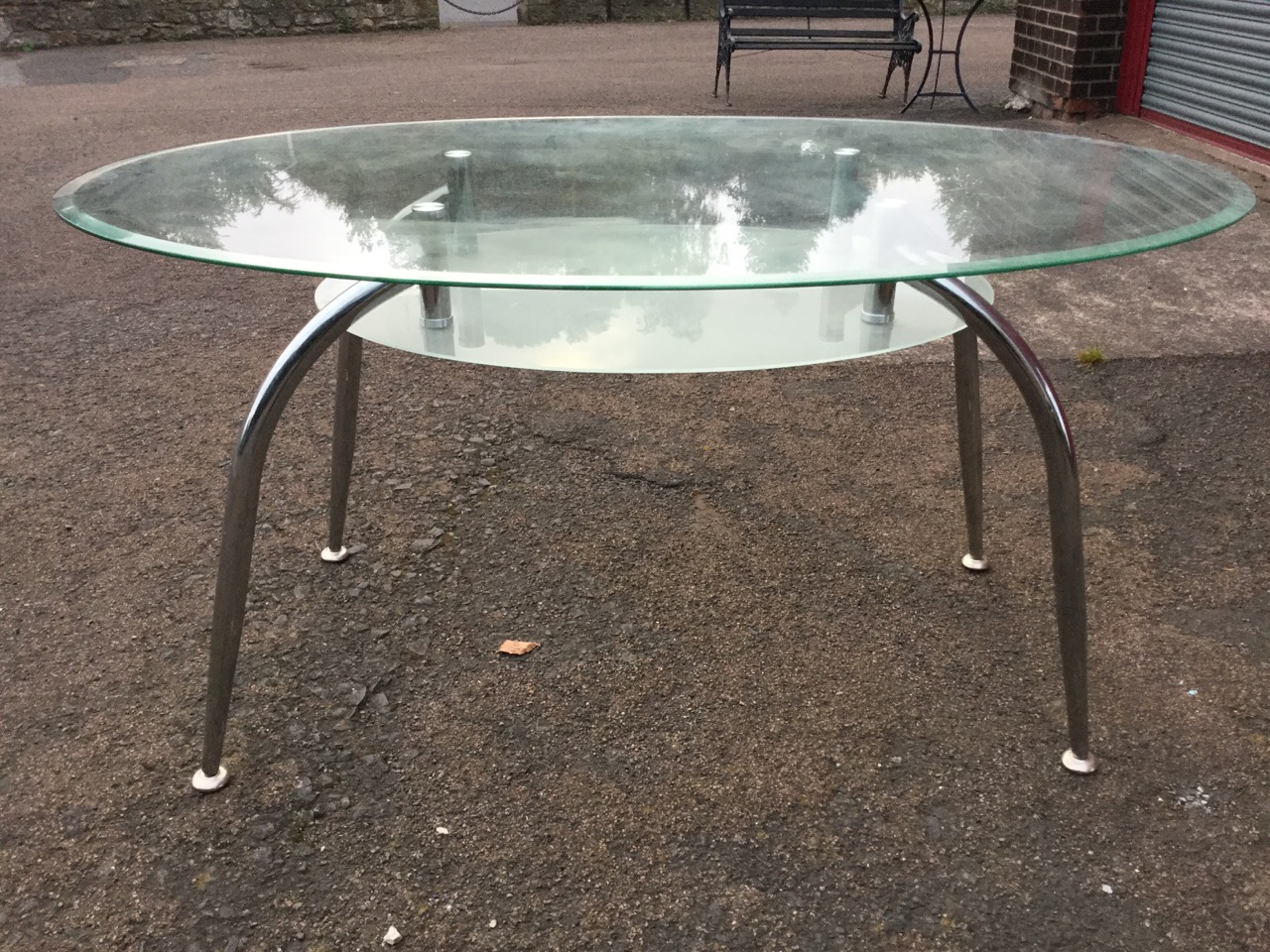Lot 39 - A contemporary oval plate glass dining table, the bevelled top with etched glass undershelf raised